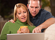 A man and woman consulting a laptop computer.